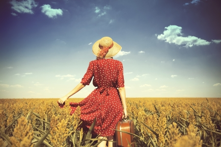 enchantress: Redhead girl with suitcase at corn field.