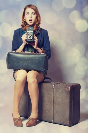 Redhead girl with camera sitting on the big suitcase photo
