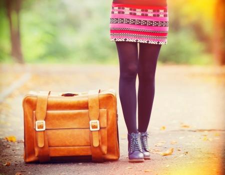 moda: Osady damskie pobliżu walizka na jesieni na świeżym powietrzu.
