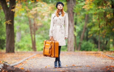 Redhead girl with suitcase at autumn outdoor. photo