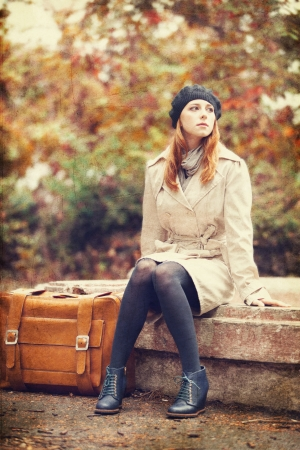 Redhead girl with suitcase sitting at autumn outdoor. photo