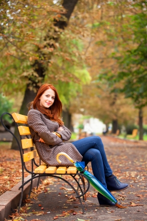 Style redhead girl sitting at bench in autumn park. photo