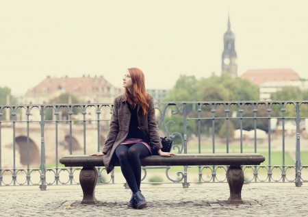 sit: Redhead girl sitting on the bench near river in Dresden. Stock Photo
