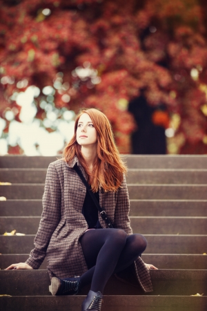 Redhead girl with sitting at outdoor. photo