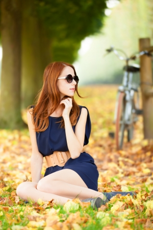 Beautiful redhead women with bike in Versailles gardens. France photo