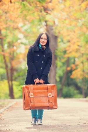 Brunette girl holding suitcase at autumn alley in the park photo