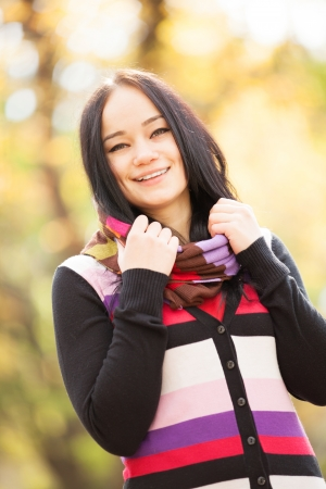 Brunette girl at autumn alley in the park photo