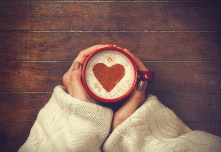 mujer tomando cafe: mujer que sostiene la taza de caf? caliente, con forma de coraz?n