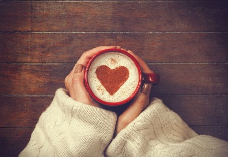 woman holding hot cup of coffee, with heart shape photo