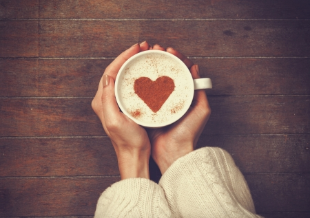 심장 모양으로, 커피의 뜨거운 컵을 들고하는 여자