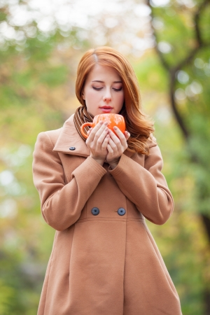 Redhead girl with cup in the park photo