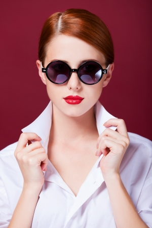 Redhead in sunglasses on red background photo