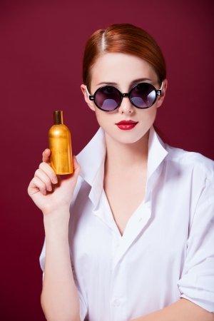 Redhead in sunglasses with perfume on red background photo