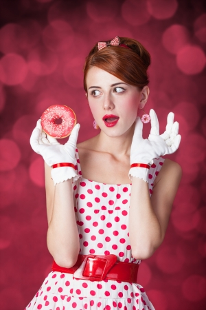 donut style: Beautiful redhead women with donut. Photo in retro style with bokeh at background.