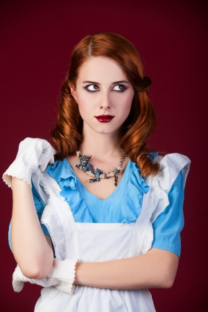 Portrait of a young redhead woman dressed as Alice in Wonderland, video game.