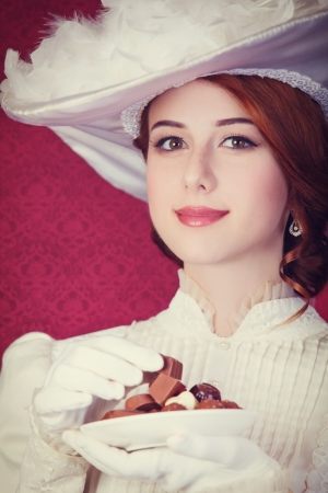 sweettooth: Beautiful redhead women with candy. Photo in retro style with bokeh at background. Stock Photo