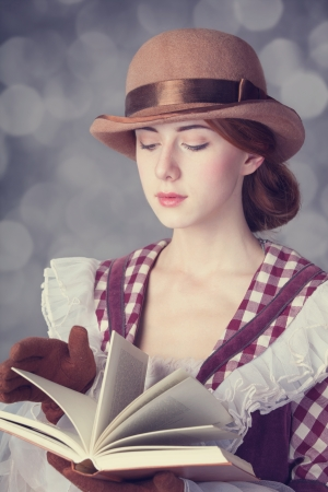 Beautiful redhead women with book. Photo in retro style with bokeh at background. photo