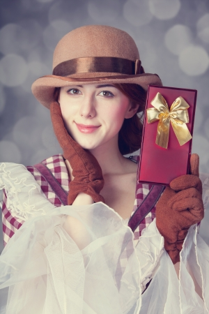 Beautiful redhead women with gift. Photo in retro style with bokeh at background. photo