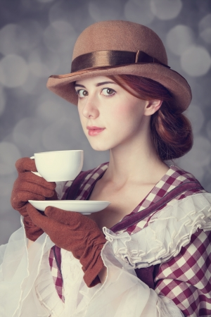 Beautiful redhead women with cup of tea. Photo in retro style with bokeh at background. photo