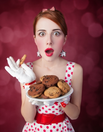 Beautiful redhead women with coockie. Photo in retro style with bokeh at background. Stock Photo