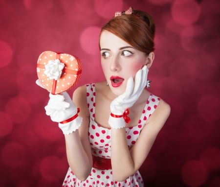 Beautiful redhead women with gift. Photo in retro style with bokeh at background. Stock Photo