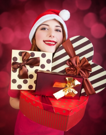 Redhead girl with gifts on red background photo