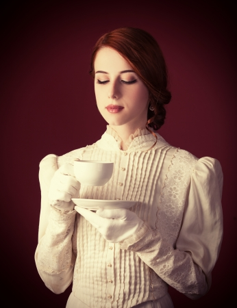 traditional dress: Beautiful redhead women with cup of tea