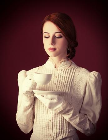 mujer elegante: Mujer bella pelirroja con la taza de t�