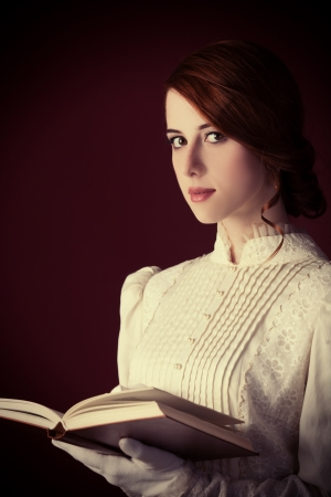 Beautiful redhead women with book photo