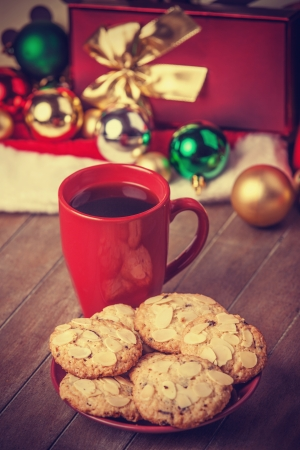 Cookies and cup of coffee with christmas gifts at background photo