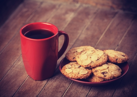 Cookies and cup of coffee with christmas gifts at backgorund photo