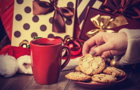 Cookies, cup of coffee and female hand with christmas gifts at background photo