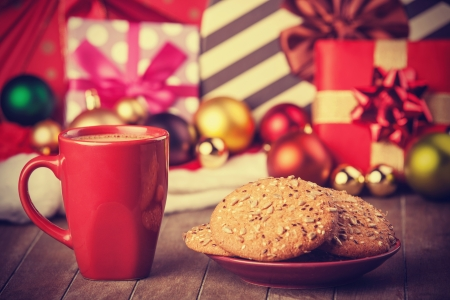 Cookies and cup of coffee with christmas gifts photo