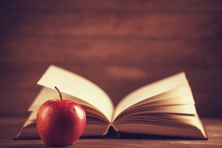 books on a wooden surface: Apple and the book. Photo in old color image style Stock Photo
