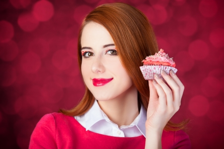 Redhead girl with cake. Photo red background with bokeh. photo