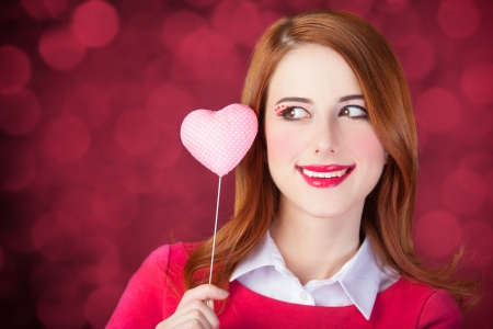 Redhead girl with shape heart toy. Photo red background with bokeh. photo