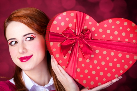 Redhead girl with shape heart box. photo