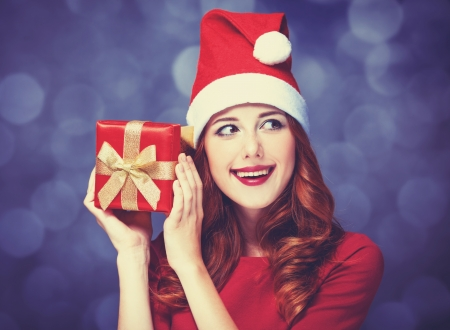 Redhead girl with gifts on purple background photo