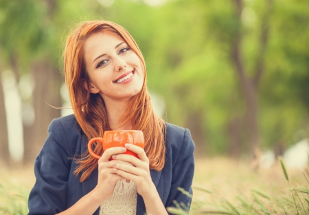 country girl: Redhead girl with orange cup at outdoor