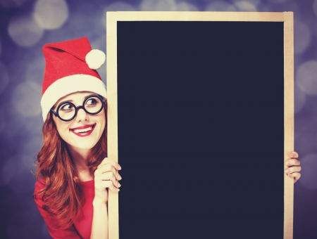 Redhead girl in christmas hat with blackboard photo