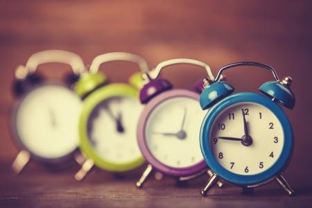 wooden clock: Retro alarm clocks on a table. Photo in retro color image style