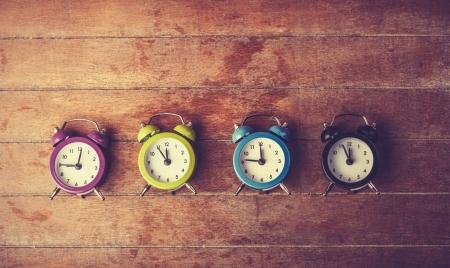 Retro alarm clocks on a table. Photo in retro color image style