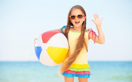 little girl beach: Little girl playing on beach with ball.
