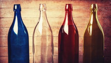 aligote: Four empty bottles of wine on wooden background Stock Photo