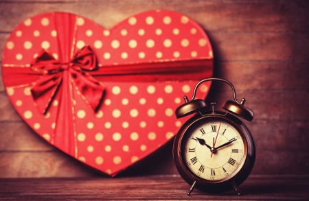 Retro clock and gift in heart shape on the background.  photo