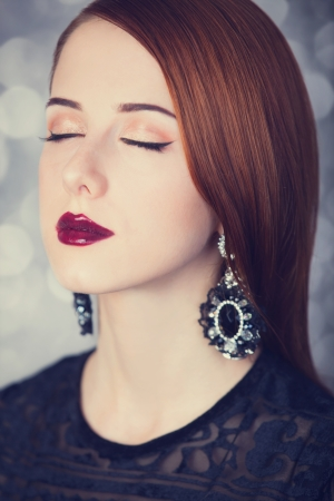 Beautiful redhead women with earrings.  photo