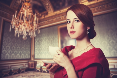 Beautiful redhead women with cup of tea. Photo in old color image style.