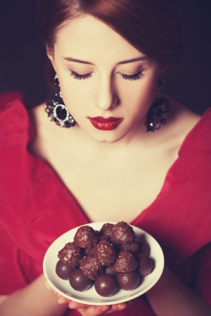 sweettooth: Beautiful redhead women with candy. Photo in retro style.