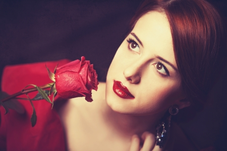 Beautiful redhead women with rose. Photo in old color image style. photo