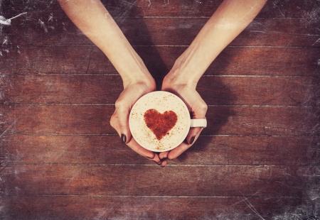 desayuno romantico: mujer que sostiene la taza de caf� caliente, con forma de coraz�n